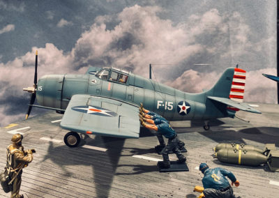 Blue shirted plane handlers maneuver a Hellcat into position prior to launch. Crowded flight decks with tightly stacked planes often dictated that manpower, not tractors, were the best option to move aircraft in tight quarters.