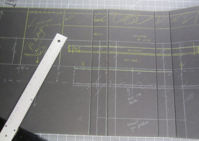 """On a 40"""" square piece of black foam board,.I sketched out a continuous front and both port and starboard sides of the main structure to minimize gluing situations. Using a V-shaped cutting tool, I carefully cut groves and bent each corner, and then reinforced with Bass wood for strength. I also built in slots for the observation decks to slide into the main structure,"""