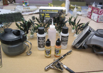 Craft store plants are airbrushed with multiple shades of greens and browns
