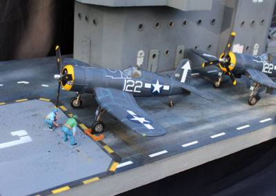 The metal elevator covers that bring the planes up from the lower decks are plastic Evergreen pieces cut to shape. I used a T-square and tape to carefully lay out the stripping before painting the deck over a base coat of grey primer.