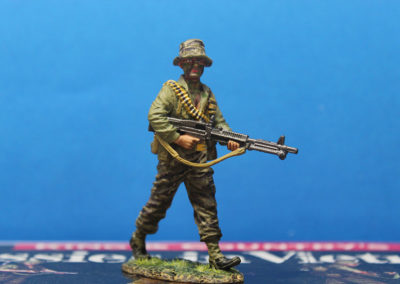 """Called the """"drag"""", the last man in line on the patrol was responsible for rear security and Carried the M-60 Machine Gun, usually with the barrel cut down to save weight. He wears a mixed uniform of tiger stripe pants and jungle fatigue shirt."""