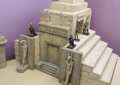 Temple two made from pink insulation foam and accessorized with King and County gate and walls, and other ancient Egyptian statues found on ebay