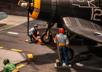 A catapult crewman in green shirt watches two plane handlers in Blue prep a Corsair prior to flight operations