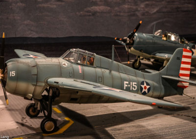 A Grumman Hellcat fighter and Douglas Dauntless dive bomber preparing for takeoff.