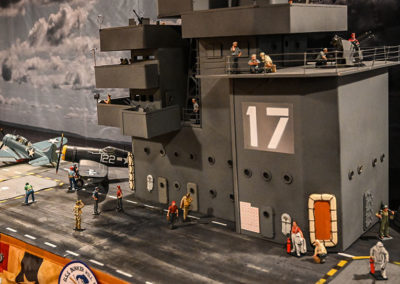 """The carriers operations """"Island"""" and John Jenkins crew prepare for aircraft launch to attack Okinawa during the invasion of that Island in 1944. The nautical elements and gray auto primer paint scheme adds realistic detail. The aircraft crane is a converted toy found on eBay."""