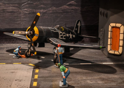 Catapult officer in green watches blue shirted ground crew prep Corsair for launch